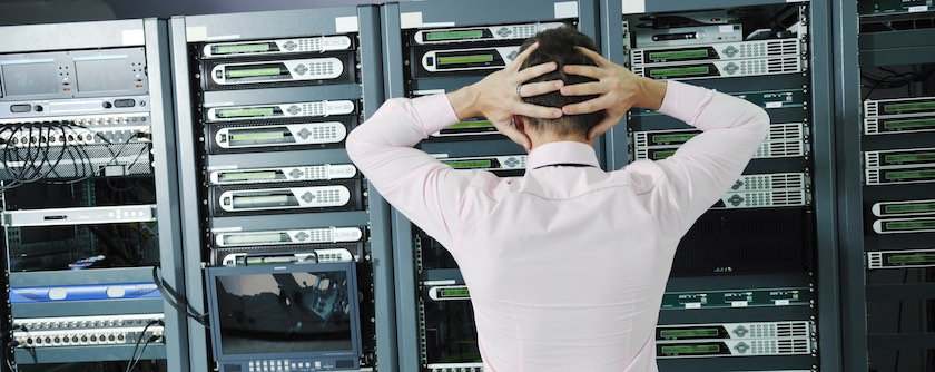 man standing in front of a rack of servers in a cloud data center